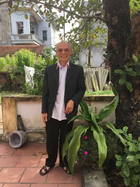 Bác Phùng bên cây Náng hoa trắng - Ảnh NVCC.